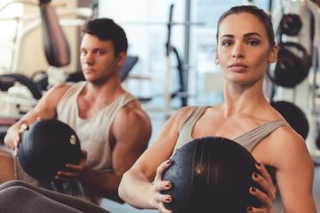man and woman working out with medicine balls