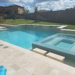 Backyard with custom pool, tile accents, and playground - Hipp Pools