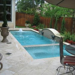 Patio with custom pool featuring two sections and water features - Hipp Pools