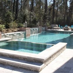 Stone courtyard with custom pool and brick accents - Hipp Pools