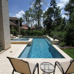 Backyard with luxurious pool, chairs, and grassy area - Hipp Pools