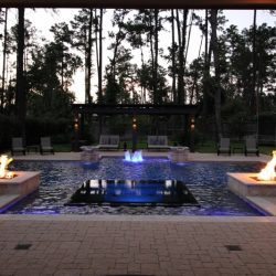 Backyard pool at night with water, fire, and light features - Hipp Pools