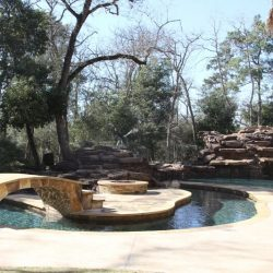 Custom pool with a bridge to a fire pit and rocks - Hipp Pools