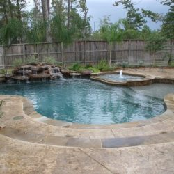 Curvy shaped pool with steps, rock waterfall, and landscaping - Hipp Pools