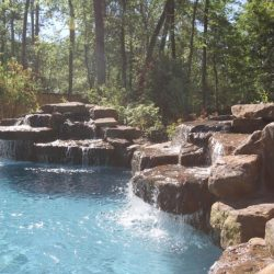 Large rock waterfalls flowing into a pool - Hipp Pools