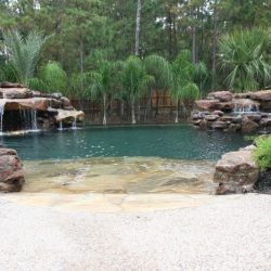 Patio sloping into a pool with rock waterfall features - Hipp Pools