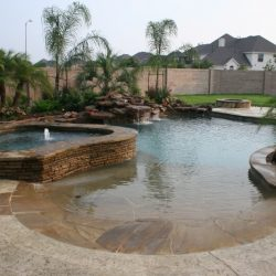Sloped patio into a pool with brick accents, rock waterfall, and trees - Hipp Pools