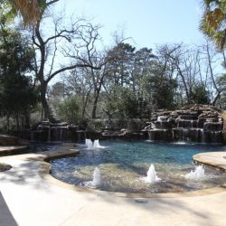 Beautiful pool with water fountains, trees, and rock water feature - Hipp Pools