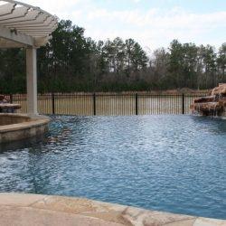 Infinity pool with pergola and rock waterfall - Hipp Pools