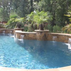 Custom pool with curved walls, water fountains, and trees - Hipp Pools
