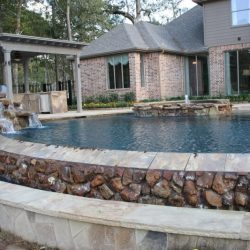 House with large custom pool overflowing over rocks - Hipp Pools