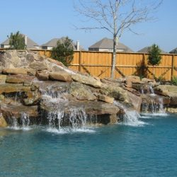 Rock waterfall feature flowing into a custom pool - Hipp Pools