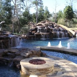 Rock waterfalls flowing into a custom pool with fire pit - Hipp Pools