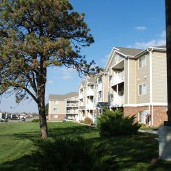 Trees and a wide expanse of grass leads up to a neat apartment building.