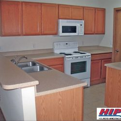 A kitchen with white appliances, light colored countertops and wood cabinets.