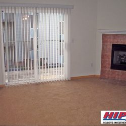 An empty living room with a red bricked fireplace and patio.