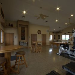 A clubhouse with tables, chairs and workout equipment.