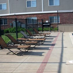 A pool with lounging chairs at an apartment complex.