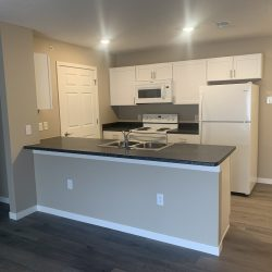 A kitchen with white cabinets, dark countertops and grey wood flooring.
