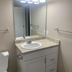 An image of a bathroom with creamy grey walls and white cabinets.