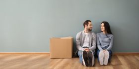 A couple sitting in an empty room with a moving box.