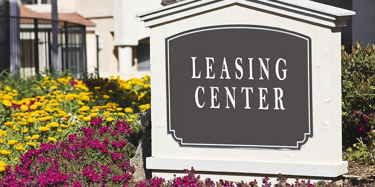 Leasing center sign surrounded by flowers.