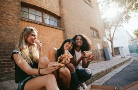 Girls happily eating pizza in alley