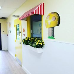 Window with flowers and mushroom wall decor - Home Away From Home West Boynton Beach daycare location