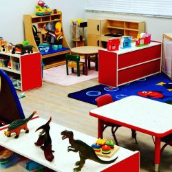 Play area with tables, carpet, and toys - Home Away From Home West Boynton Beach daycare location