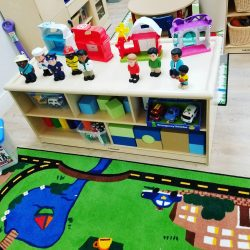 Play area with toys and fun carpet - Home Away From Home West Boynton Beach daycare location