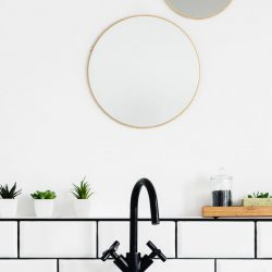 round mirror on wall over sink