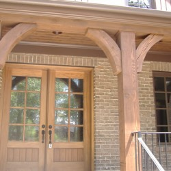 Wood accents complement a brick facade on this Chicago home remodeling project by Home Services Direct.