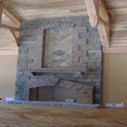 This intricate fireplace contrasts with the wood accents to bring drama to this Chicago house remodeling project by Home Services Direct.