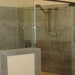 Half glass walls bring a modern touch to this bathroom remodel by Home Service Direct.