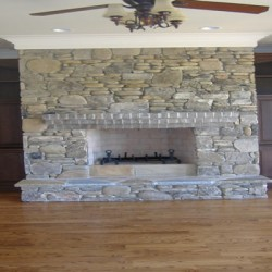 This large natural stone fireplace is a statement piece in this Chicago house remodeling project by Home Services Direct.