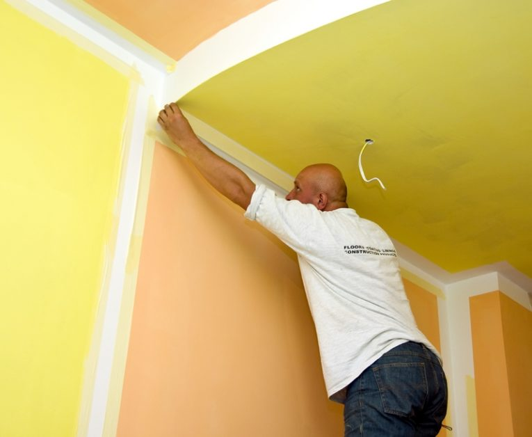 Painter Removing Tape on Walls With Gaudy Colors