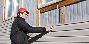 Worker Installing Siding on Home