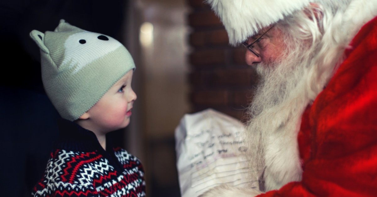 Image of a little boy talking to Santa Claus.