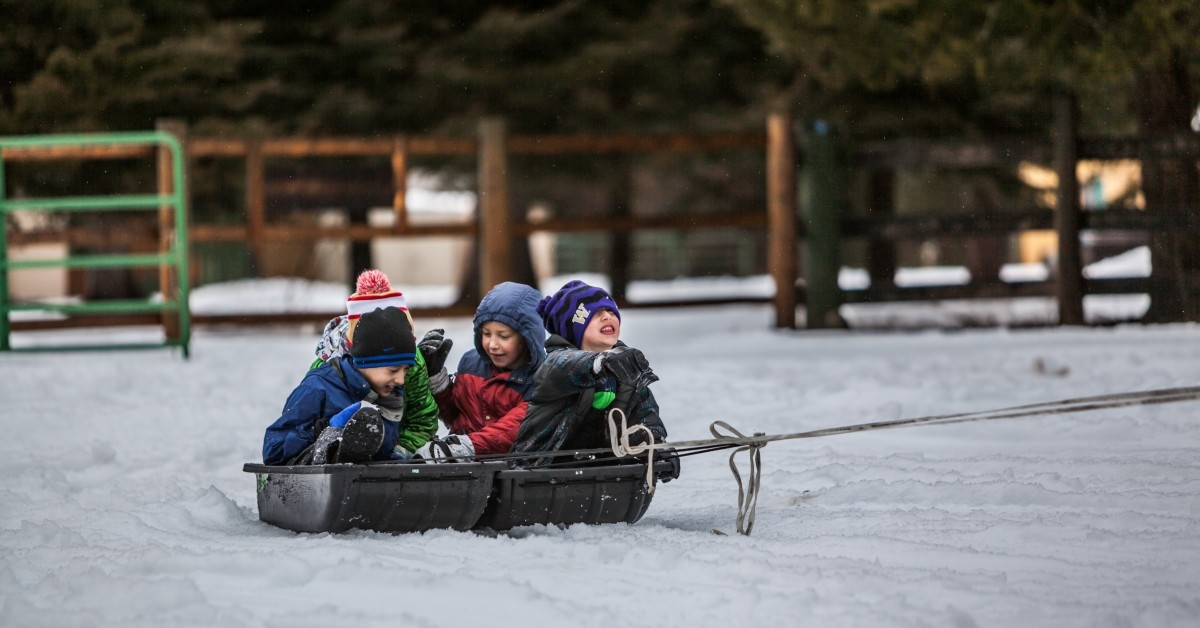 Image of four children being pulled in a sled surrounded by snow.