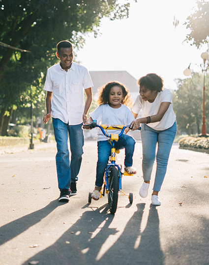 Parents teaching daughter to ride a bike