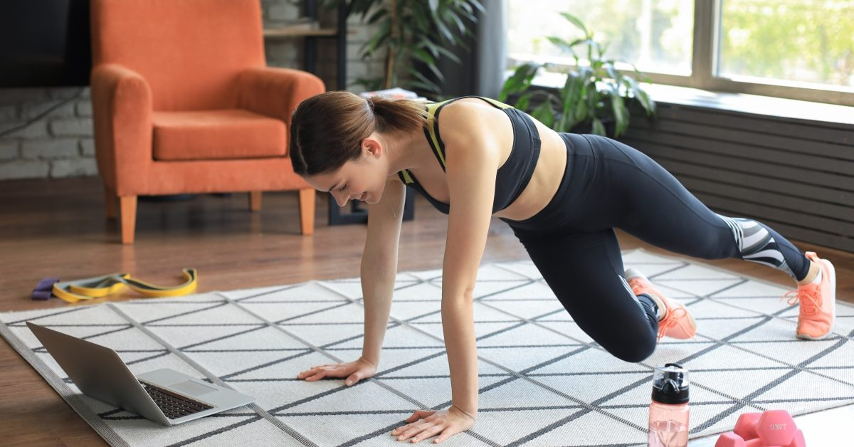 Woman working out at home to online fitness class