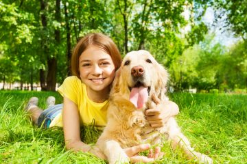 girl smiling with dog at the park