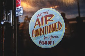 Sign at a business that reads We're Air Conditioned For Your Comfort.
