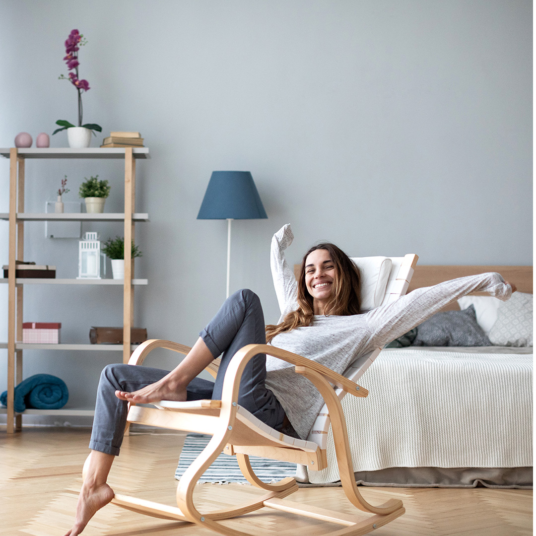 A woman sitting comfortably in her bedroom