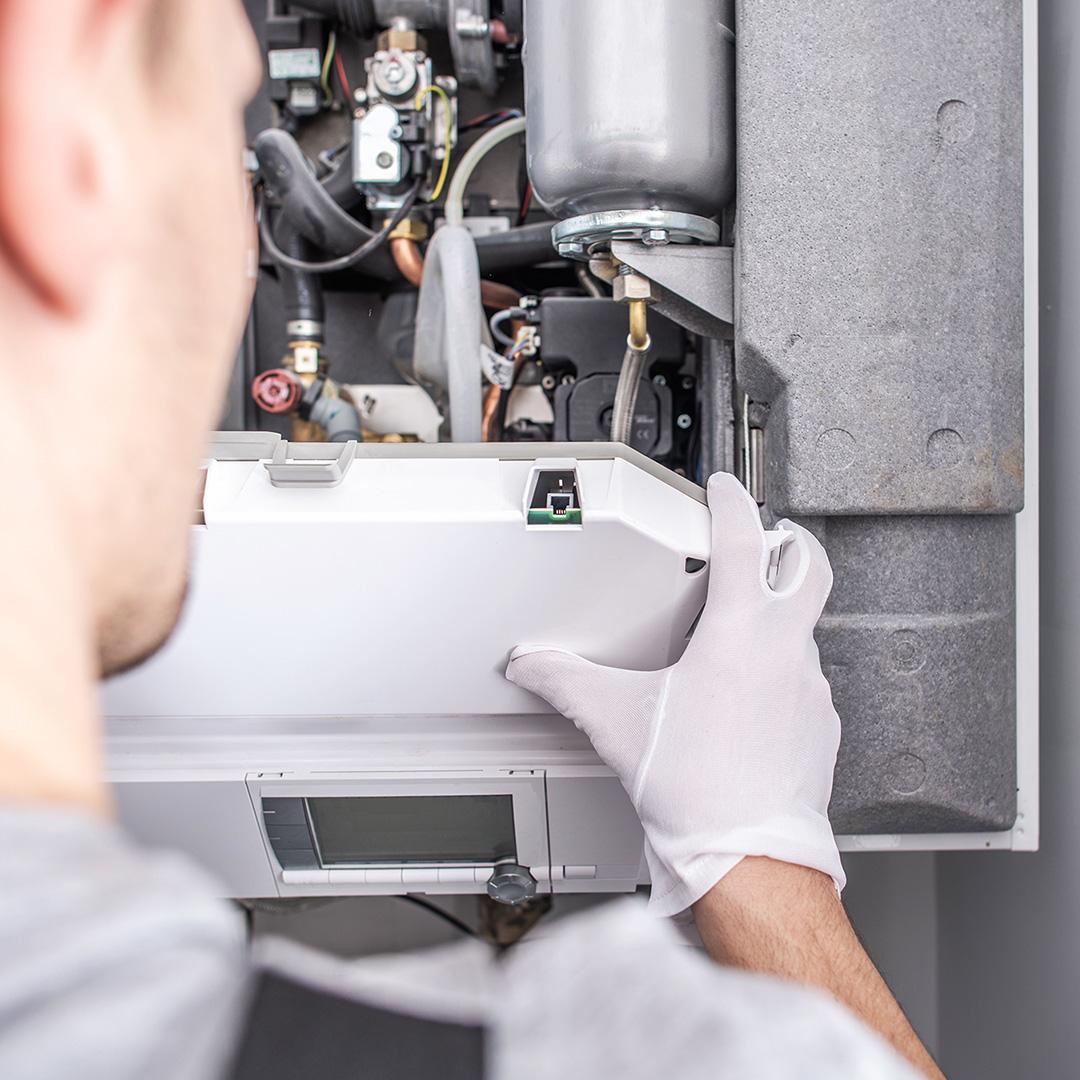 A HVAC technician working on a furnace
