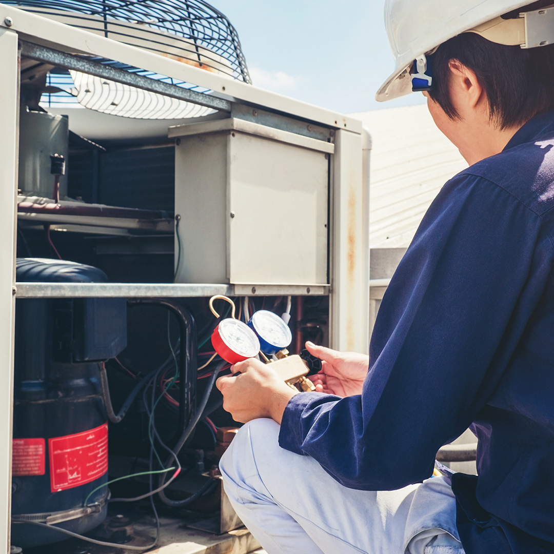 A HVAC technician working on an air conditioning unit.