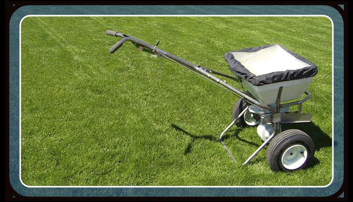 Image of a fertilizer spreader on a grass lawn.