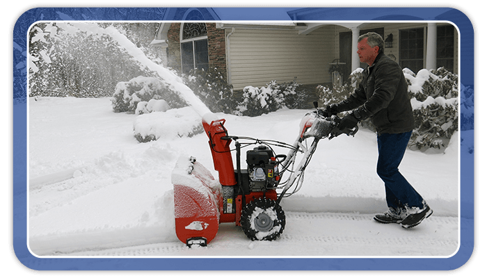 Image of a man using a snowblower to clear his driveway