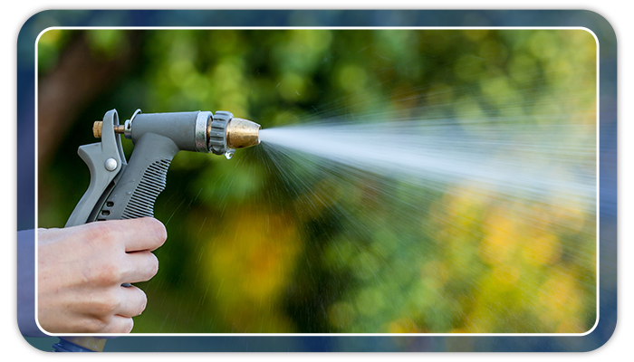 Image of a hand holding a garden hose that is spraying water.