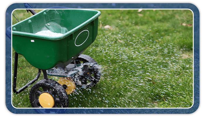 Image of a fertilizer spreader fertilizing a lawn